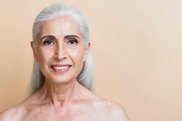Gros plan heureuse femme senior avec des cheveux gris