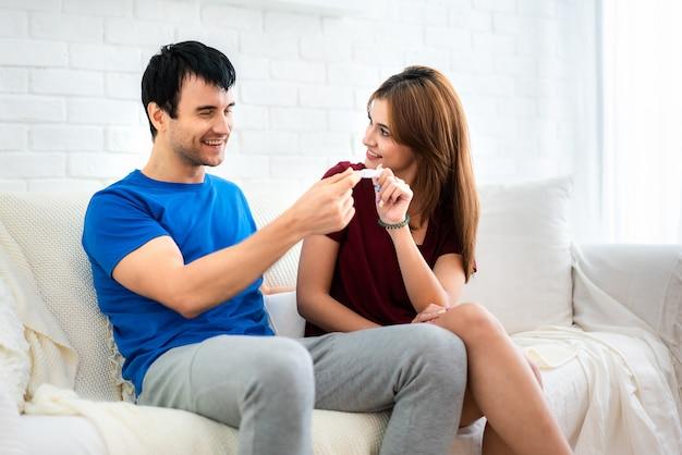 Gros plan d'heureuse jeune femme embrassant l'homme après le test de grossesse positif assis à côté de son mari dans la chambre