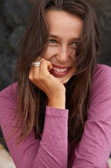 Gros plan de l'heureuse jeune femme de race blanche aux cheveux noirs exprime des émotions sincères positives