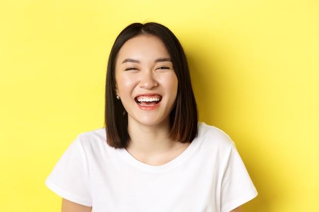 Gros plan de l'heureuse jeune femme s'amusant, souriant et riant sans soucis, debout en t-shirt blanc sur jaune