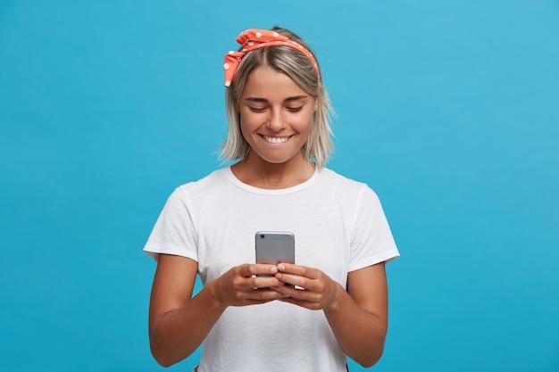 Gros plan de l'heureuse jolie jeune femme blonde porte un t-shirt blanc