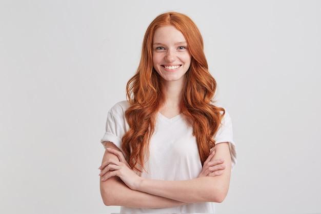 Gros plan de l'heureuse jolie jeune femme rousse aux longs cheveux ondulés