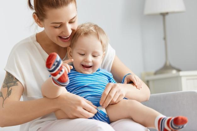 Gros plan de l'heureuse mère et enfant à la maison. jeune femme boutonner des vêtements pour enfants, tenant soigneusement son fils sur ses jambes. mignon petit garçon aux cheveux blonds dans des chaussettes colorées en regardant ses mouvements.