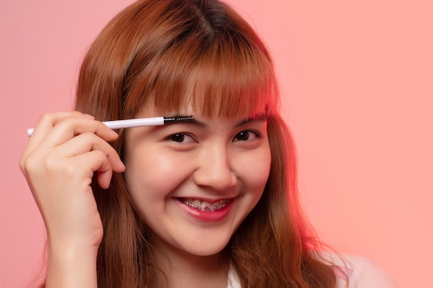 Gros plan heureux beau visage de fille appliquant le fard à paupières