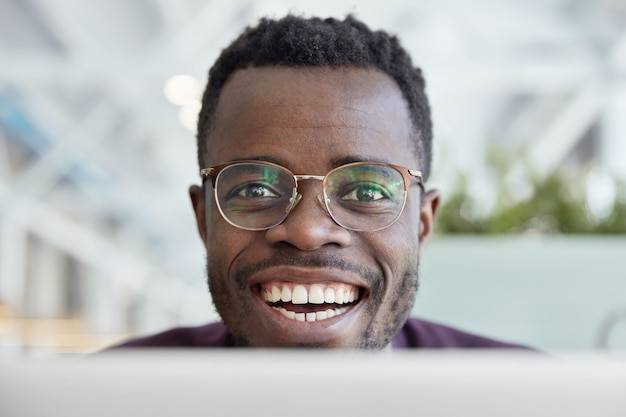 Gros plan de l'heureux homme à la peau sombre avec un large sourire, des dents blanches, porte des lunettes transparentes pour une bonne vision