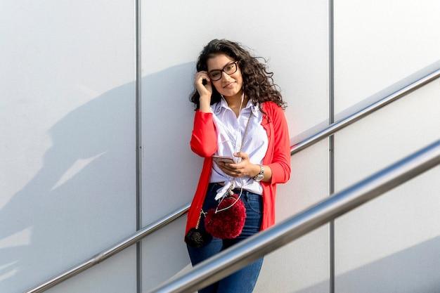 Gros plan heureux jeune femme parlant avec téléphone portable à l'extérieur en ville