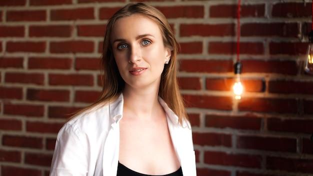 Gros plan heureux jeune femme portant une chemise blanche décontractée