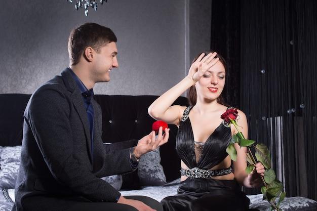 Gros plan heureux jeune homme offrant un cadeau de bijoux à sa dame accablée pendant que les deux sont assis sur le lit.