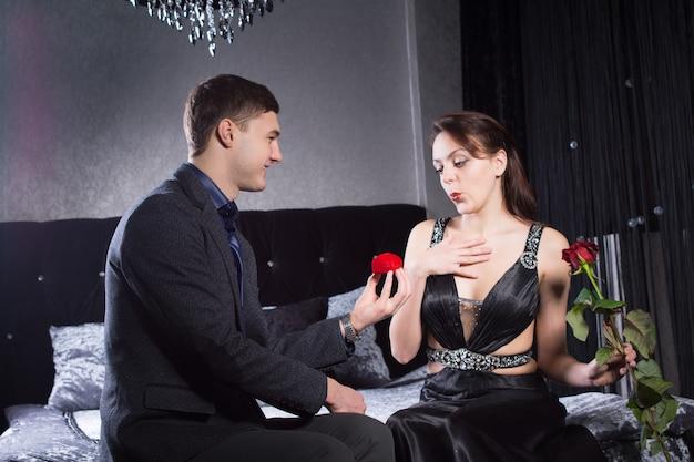 Gros plan heureux jeune homme offrant un cadeau de bijoux à sa petite amie sexy pendant que les deux sont assis sur le lit.