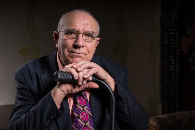 Gros plan heureux vieil homme d'affaires chauve portant des lunettes, tenant sa canne tout en appuyant son menton sur sa main et souriant à la caméra.