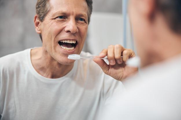 Gros plan homme adulte concentré avec une bouche ouverte debout devant le miroir