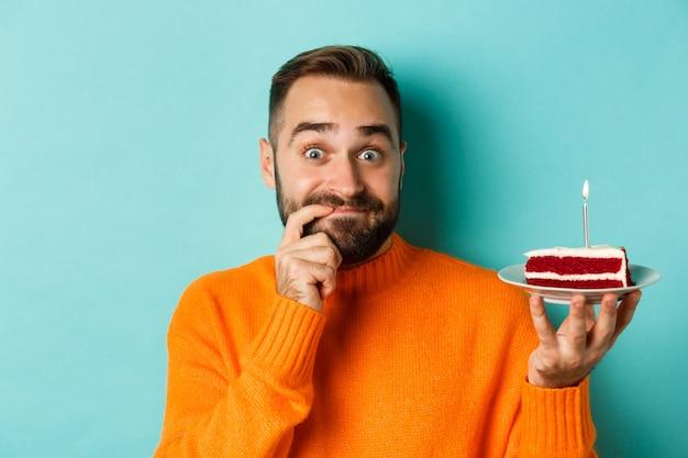 Gros plan d'un homme adulte heureux célébrant son anniversaire, tenant un gâteau bday avec bougie et souhaitant, debout sur fond turquoise.