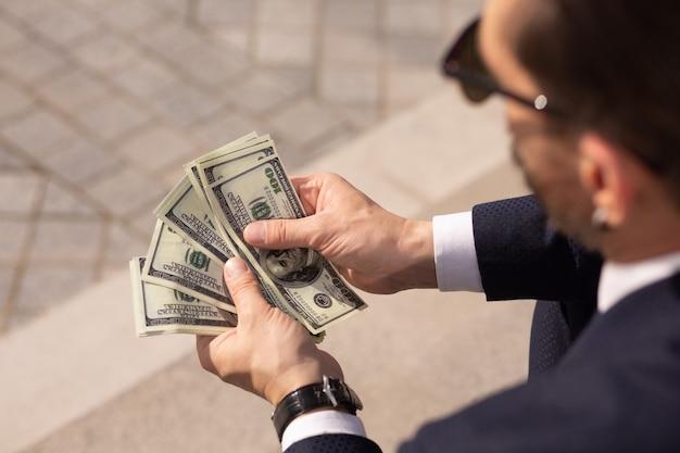 Gros plan d'un homme d'affaires américain prospère considérant liasse de billets de 100 dollars alors qu'il était assis