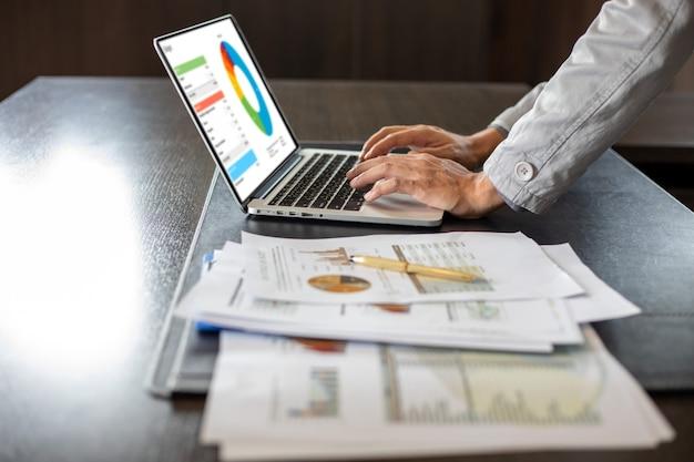 Gros plan sur un homme d'affaires asiatique utilisant des documents d'analyse d'ordinateur portable et un diagramme financier graphique sur le travail de la table de bureau