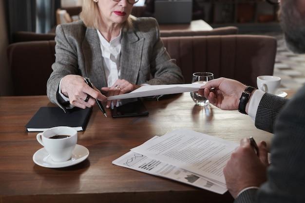 Gros plan sur un homme d'affaires assis à la table et lisant des documents lors d'une réunion avec son partenaire au restaurant