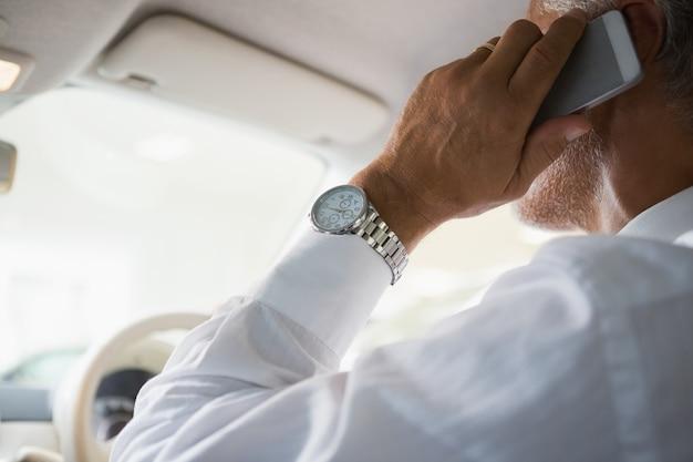 Gros plan d'un homme d'affaires au téléphone dans sa voiture