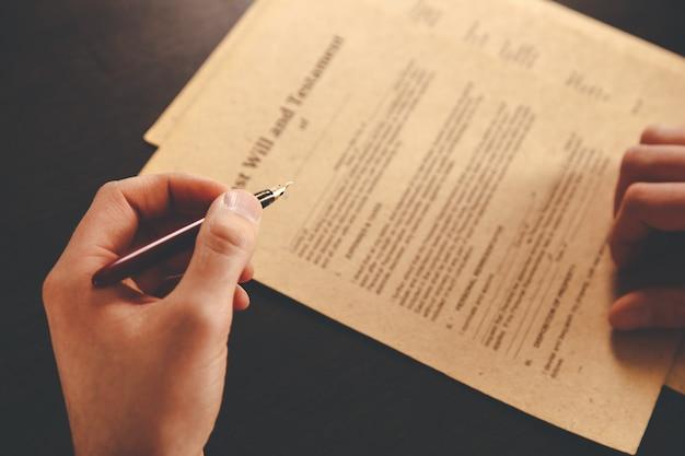 Gros plan sur un homme d'affaires avocat travaillant ou lisant un livre de droit sur le lieu de travail du bureau pour le concept d'avocat consultant.