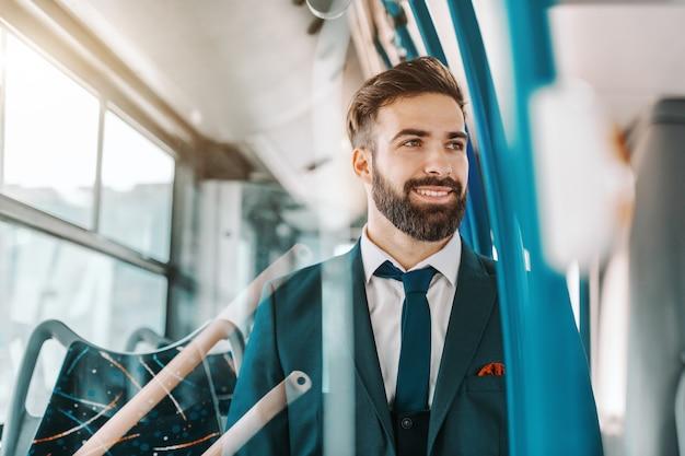 Gros plan d'un homme d'affaires barbu souriant en tenue de soirée assis dans les transports en commun et regardant par la fenêtre.