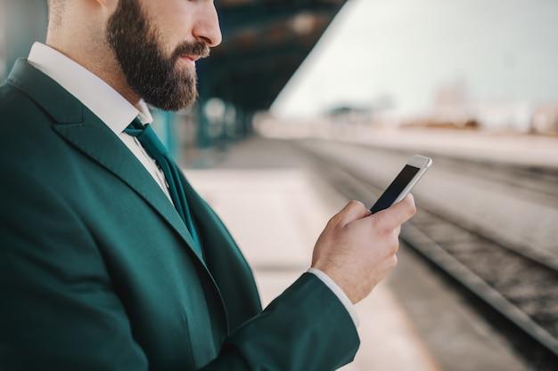 Gros plan d'homme d'affaires caucasien barbu sérieux en costume turquoise à l'aide de téléphone intelligent pour lire ou écrire un message en attendant le train. continuez à vous présenter lorsque la plupart des gens arrêtent.