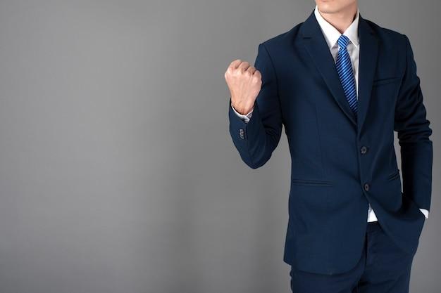 Gros plan d'un homme d'affaires en costume bleu réussit sur fond gris