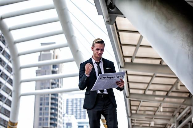 Gros plan d'un homme d'affaires dans une suite noire lisant les dernières nouvelles