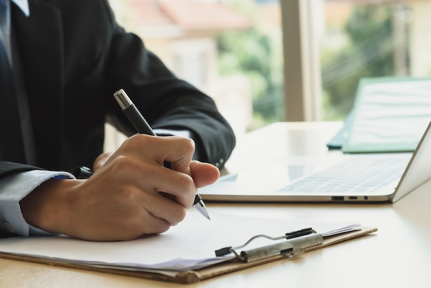 Gros plan de l'homme d'affaires écrivant ou signant un contrat sur papier au bureau.