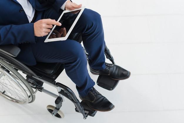Gros plan, homme affaires, main, roue, fauteuil roulant