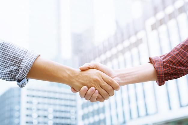 Gros plan d'un homme d'affaires main serrer l'investisseur entre deux collègues ok, réussir en affaires main dans la main.