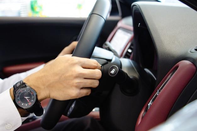 Gros plan un homme d'affaires mains mettre une montre tenant le volant avec console rouge.