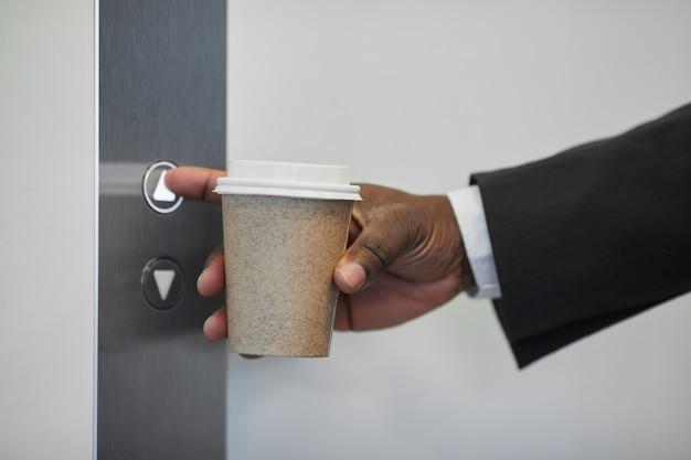 Gros plan d'un homme d'affaires méconnaissable appuyant sur le bouton de l'ascenseur dans un immeuble de bureaux et tenant une tasse de café recyclable, espace de copie