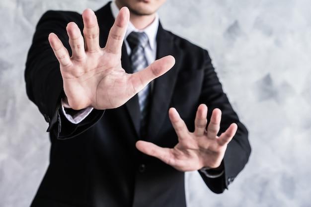 Gros plan d'homme d'affaires montrant handsign palm sur fond grunge.