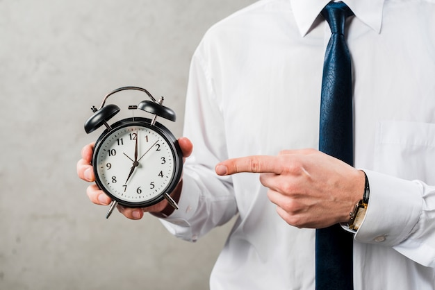 Gros plan, homme affaires, pointage, doigt, temps, contre, mur gris