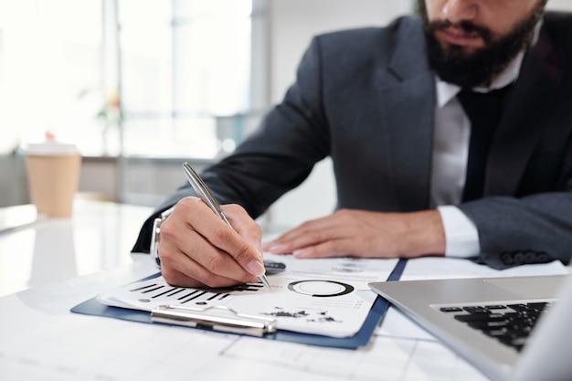Gros plan d'un homme d'affaires prospère méconnaissable écrit sur le presse-papiers remplissant des graphiques de données et des tableaux tout en travaillant au bureau, copiez l'espace
