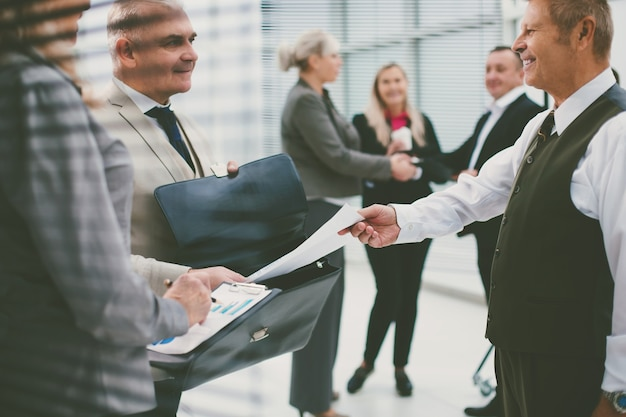 Gros plan sur un homme d'affaires prospère remettant un document à son partenaire commercial