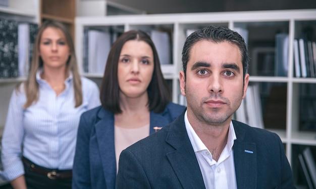 Gros plan d'un homme d'affaires regardant la caméra avec deux collègues féminines en arrière-plan