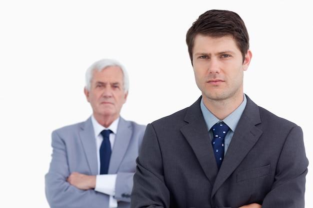 Gros plan d'un homme d'affaires sérieux avec son mentor derrière lui