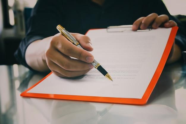 Gros plan de l'homme d'affaires en signant un contrat faisant une affaire.