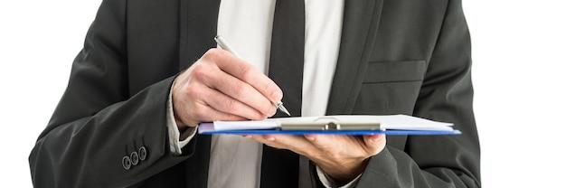 Gros plan d'un homme d'affaires tenant un dossier bleu du presse-papiers, écrivant des notes et des observations avec un stylo à encre.