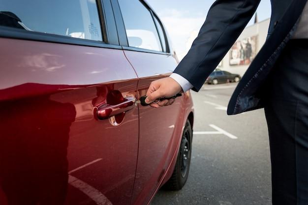 Gros plan d'un homme d'affaires tirant la poignée de porte de voiture