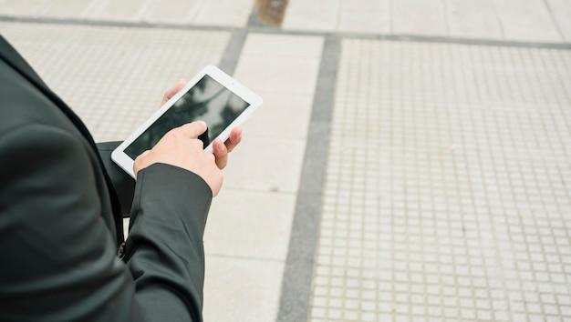 Gros plan d'un homme d'affaires touchant le téléphone intelligent avec le doigt