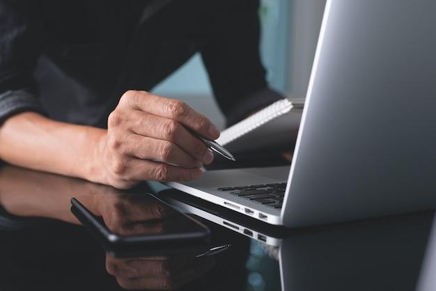 Gros plan d'un homme d'affaires travaillant sur un ordinateur portable au bureau