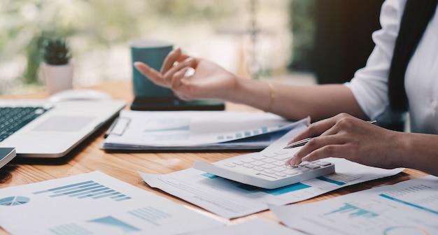 Gros plan sur un homme d'affaires utilisant une calculatrice et un ordinateur portable pour calculer le concept de finance, d'impôt, de comptabilité, de statistiques et de recherche analytique