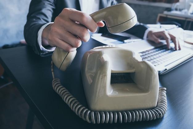 Gros plan d'homme d'affaires en utilisant le téléphone tout en travaillant sur le bureau.