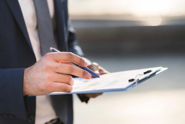 Gros plan, homme affaires, vérification, presse-papiers