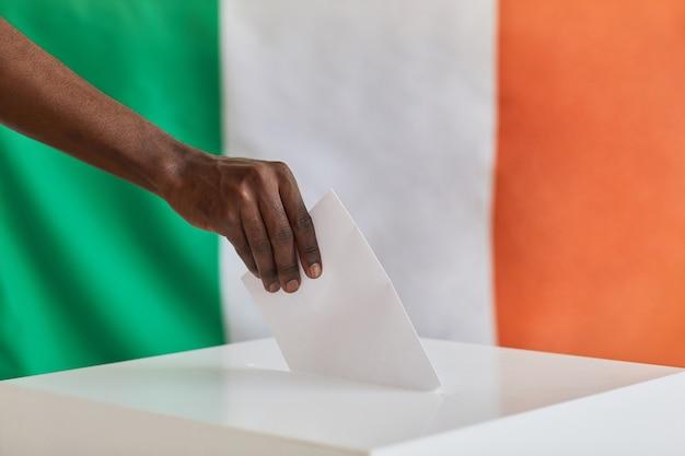 Gros plan d'un homme africain mettant l'enveloppe dans la boîte au bureau de vote