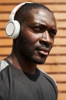 Gros plan d'un homme africain pensif écoutant de la musique dans des écouteurs à l'extérieur