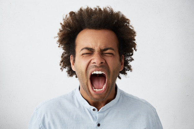 Gros plan d'un homme afro-américain aux cheveux touffus et à la peau pure ayant fermé les yeux et la bouche grande ouverte