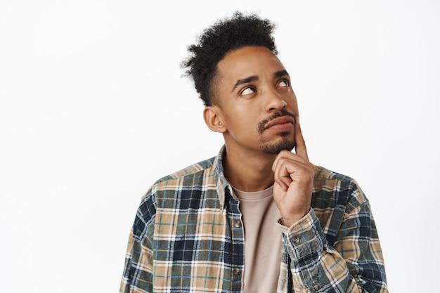 Gros plan d'un homme afro-américain réfléchi prenant une décision, étudiant pensant à smth, toucher la mâchoire et levant les yeux, méditer sur les choix, debout sur blanc
