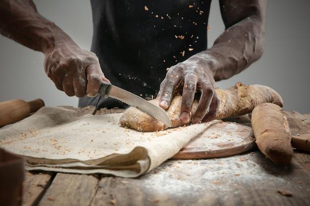 Gros plan de l'homme afro-américain tranches de pain frais avec un couteau de cuisine