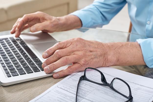 Gros plan d'un homme âgé méconnaissable assis à table et utilisant un service en ligne sur ordinateur portable